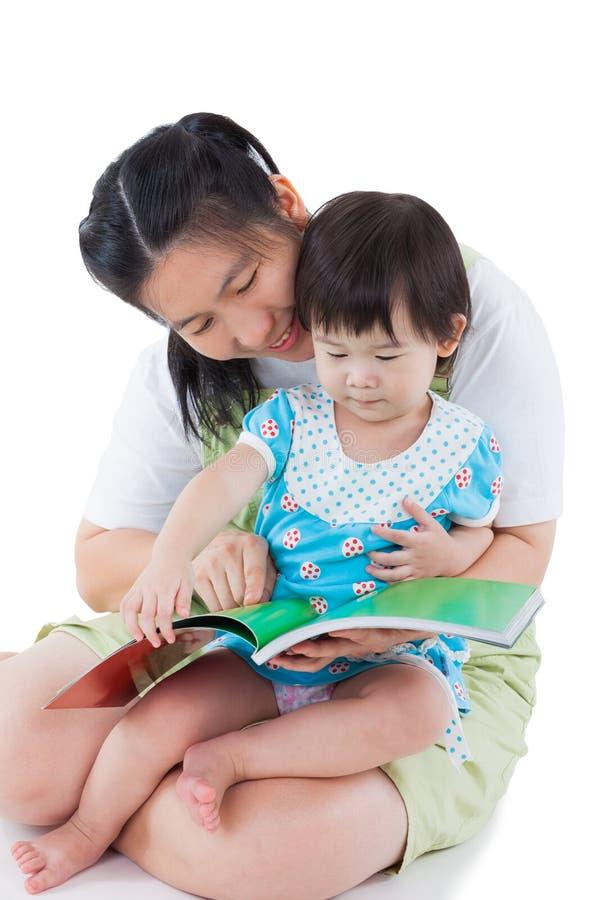 Giovane femmina con la piccola ragazza asiatica che legge un libro immagine stock