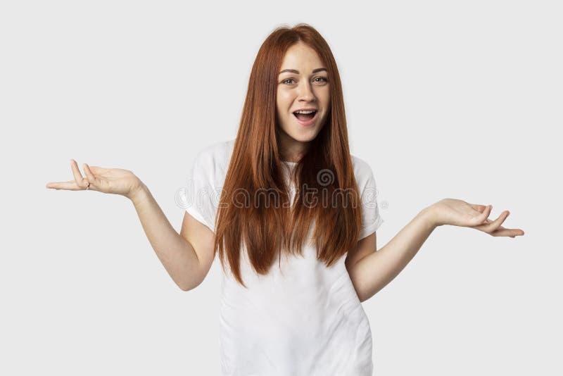 Giovane femmina europea emozionale isolata su fondo grigio La ragazza dai capelli rossi sorride in una maglietta bianca Mostra la fotografie stock