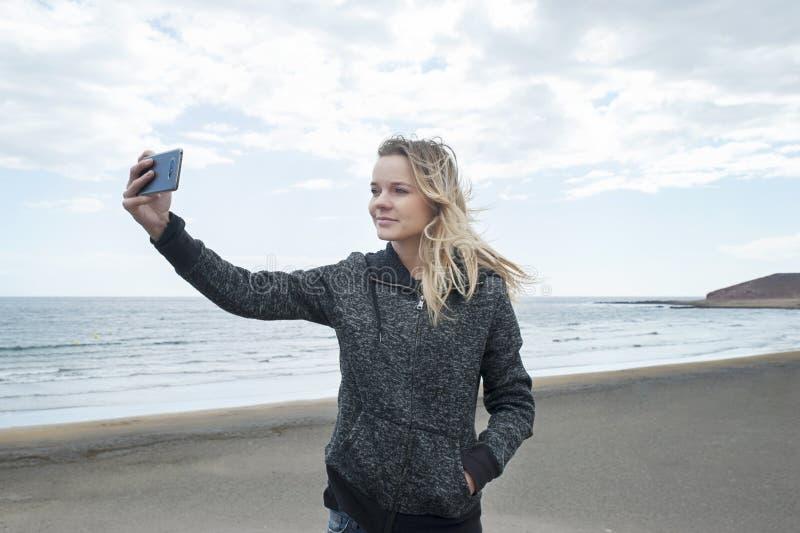 Giovane femmina millenaria di etnia caucasica che prende un selfie alla spiaggia di EL Medano, Tenerife, isole Canarie, Spagna fotografie stock libere da diritti