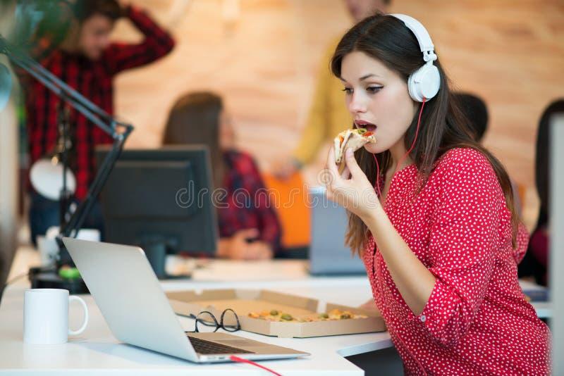 Giovane femmina nel gruppo della call center che mangia pizza immagini stock