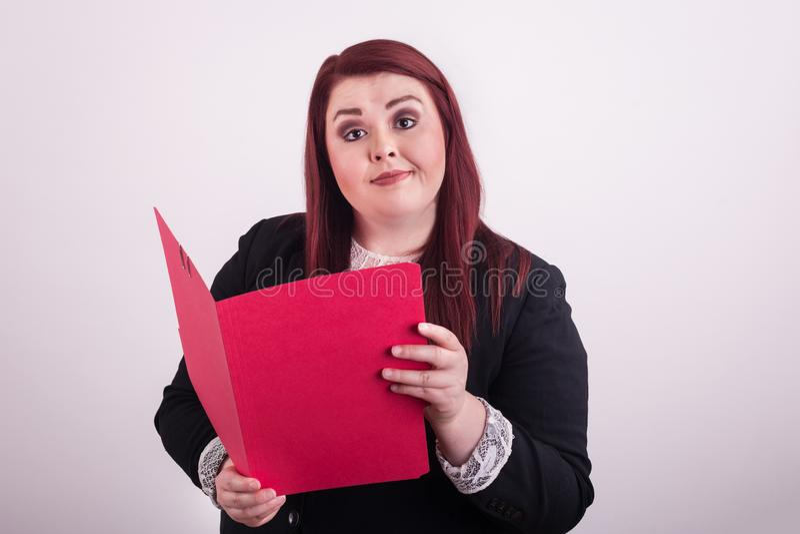 Giovane femmina professionale tenendo aperto una cartella di archivio rossa che indica  immagine stock
