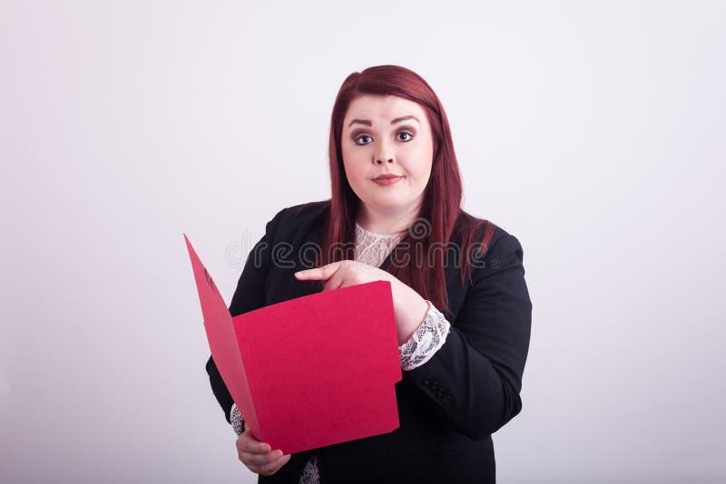 Giovane femmina professionale tenendo aperto una cartella di archivio rossa che indica  fotografie stock