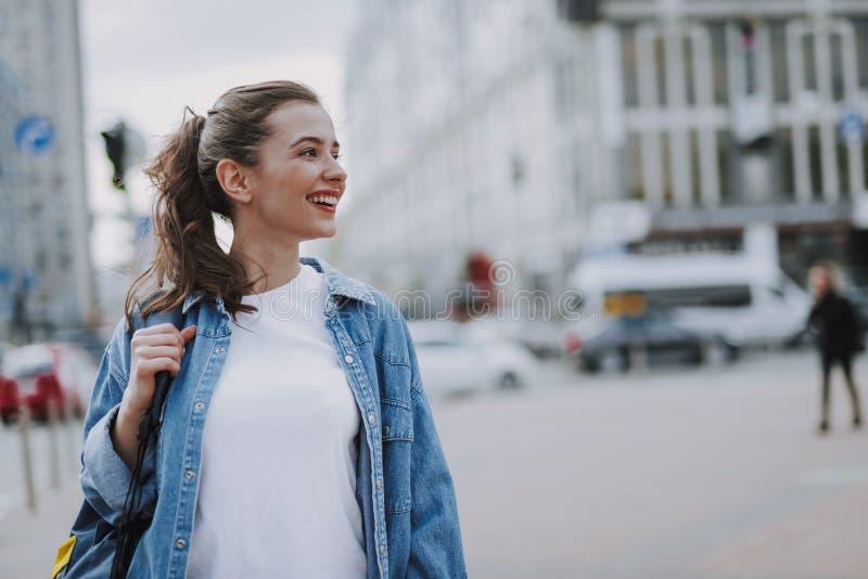 Giovane femmina sorridente graziosa che cammina intorno alla città fotografia stock libera da diritti