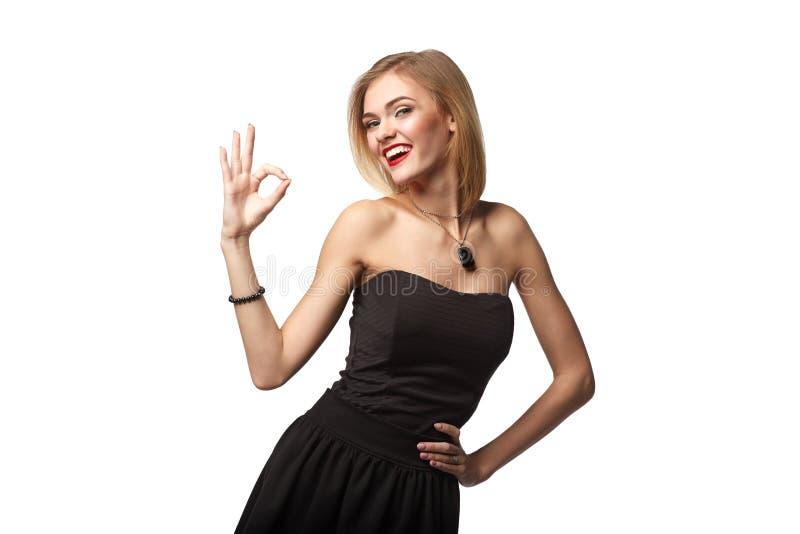 Giovane femmina teenager che mostra gesturing OKAY contro il fondo bianco immagine stock