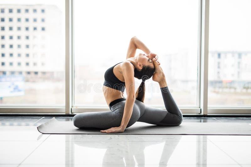 Giovane finestra panoramica di pratica sorridente attraente di agaist di yoga della donna, sedentesi in un esercizio fornito di g fotografie stock libere da diritti