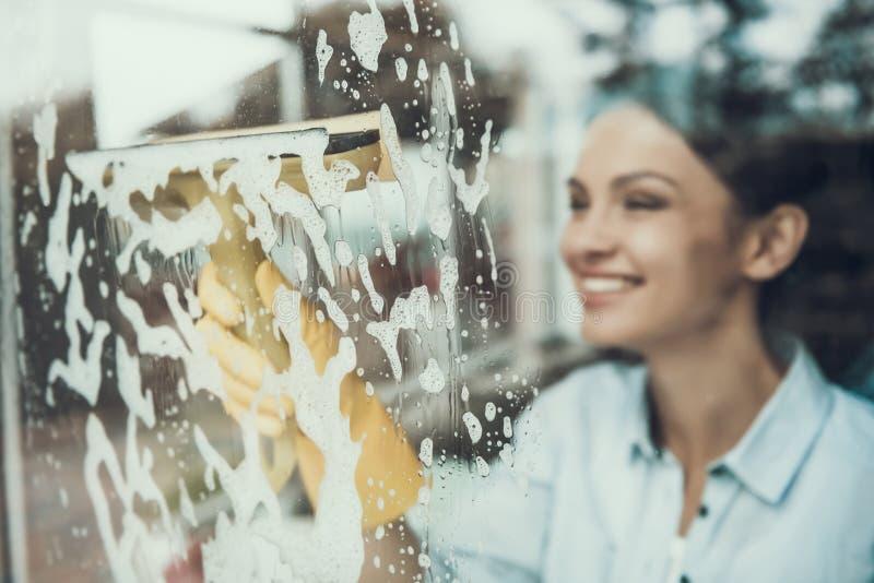 Giovane finestra sorridente di lavaggio della donna con la spugna fotografia stock