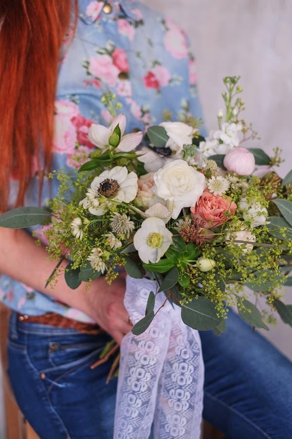 Giovane fiorista femminile che tiene un mazzo floreale di fioritura appena fatto dei garofani rosa pastelli e dell'eucalyptus con fotografia stock libera da diritti