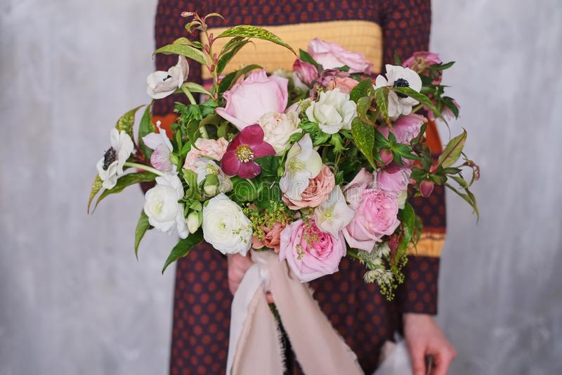 Giovane fiorista femminile che tiene un mazzo floreale di fioritura appena fatto dei garofani rosa pastelli e dell'eucalyptus con fotografia stock