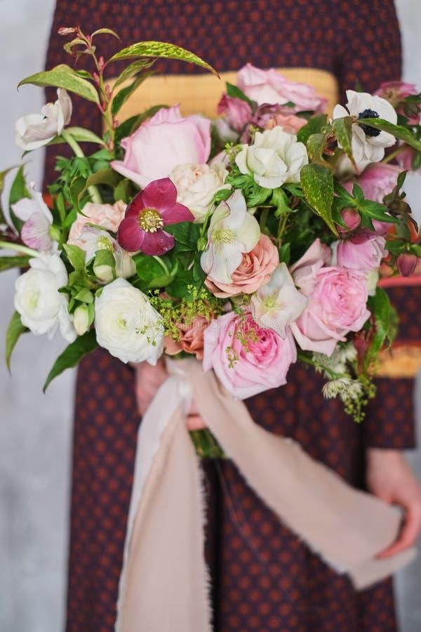 Giovane fiorista femminile che tiene un mazzo floreale di fioritura appena fatto dei garofani rosa pastelli e dell'eucalyptus con immagine stock