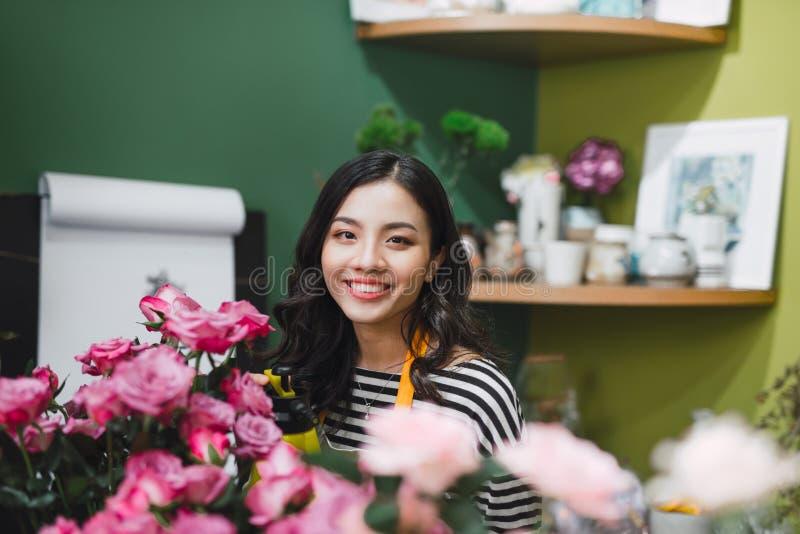 Giovane fiorista femminile concentrato sveglio che lavora nel negozio di fiore fotografia stock libera da diritti