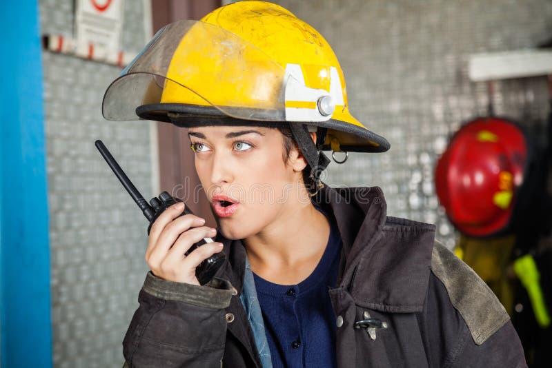 Giovane Firewoman facendo uso del walkie-talkie a fuoco immagine stock