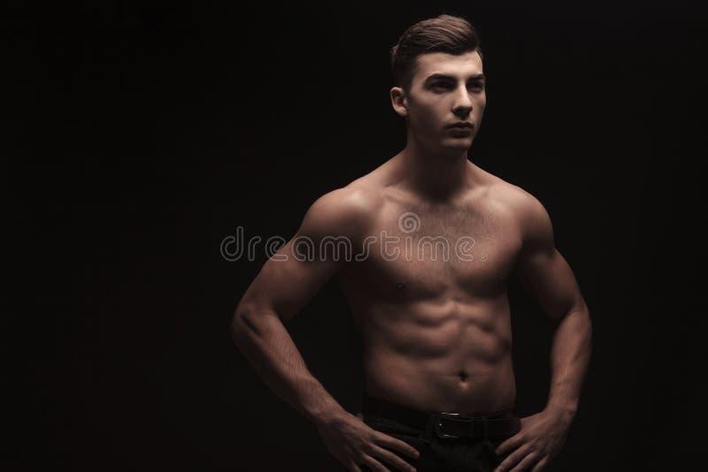 Giovane flessione maschio nel fondo scuro dello studio con le mani sulla vita fotografia stock libera da diritti