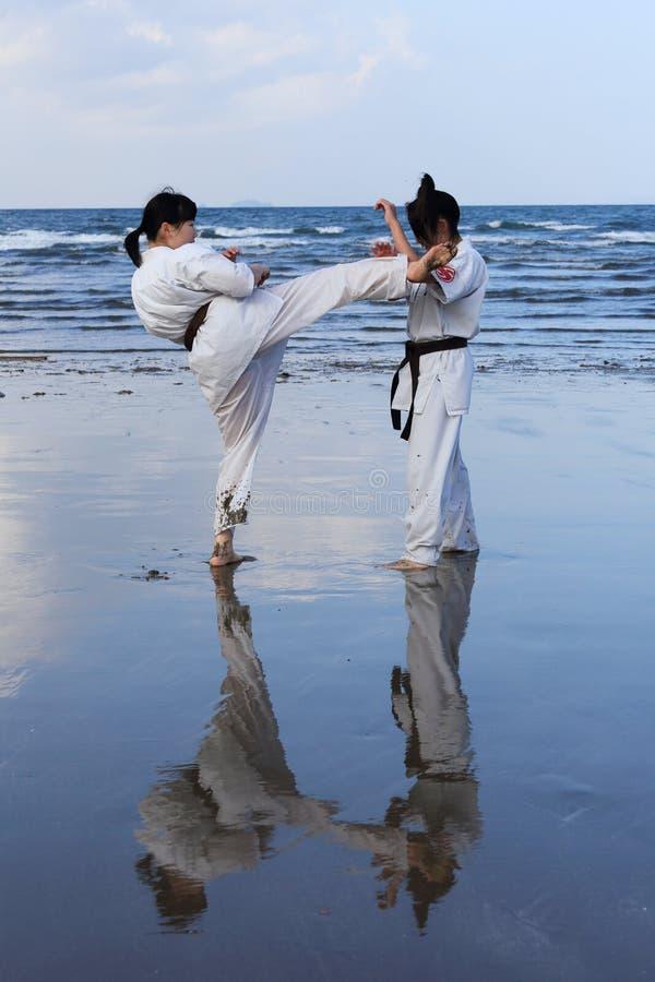 Giovane formazione giapponese delle ragazze del karatè alla spiaggia fotografie stock libere da diritti