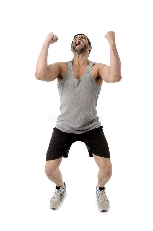 Giovane forte ed uomo adatto di sport che celebra vittoria sulla corsa corrente fotografia stock