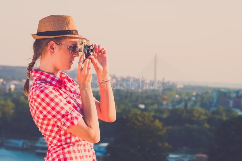 Giovane foto di presa turistica femminile della città al tramonto immagine stock