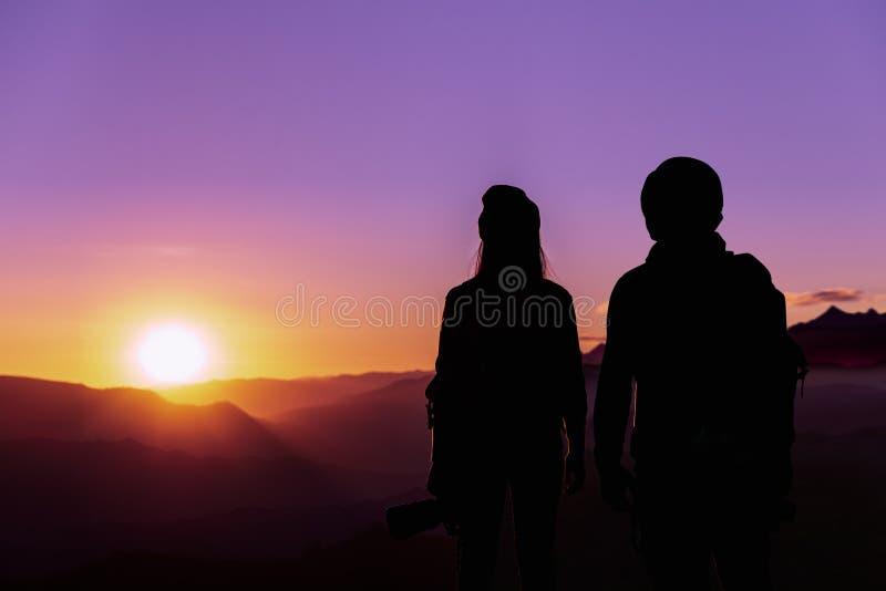 Giovane fotografo dei pantaloni a vita bassa che tiene la macchina fotografica con il tramonto sullo sfondo naturale della montag fotografie stock libere da diritti