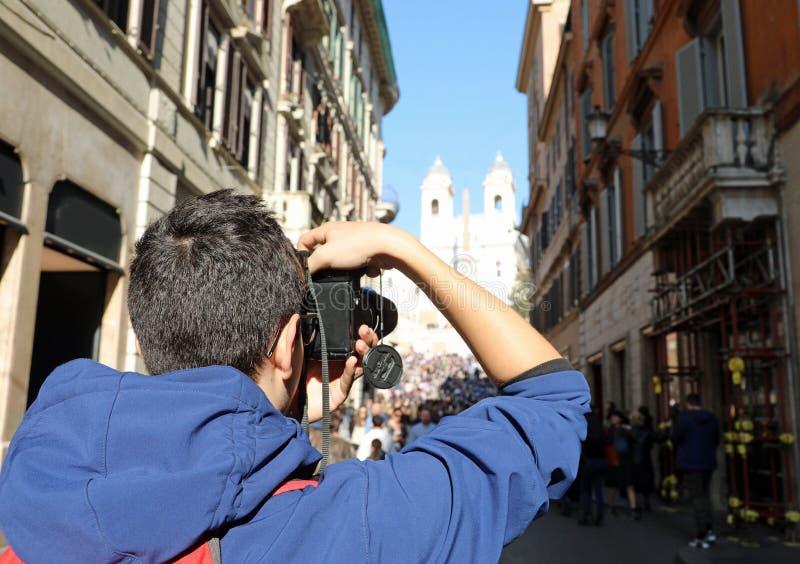 Giovane fotografo dentro via il dei Condotti a Roma e la chiesa i immagine stock libera da diritti