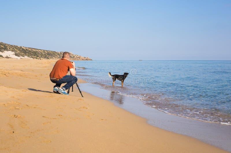 Giovane fotografo e videographer che fanno le foto e video del mare ed il suo cane con la macchina fotografica su un treppiede immagini stock