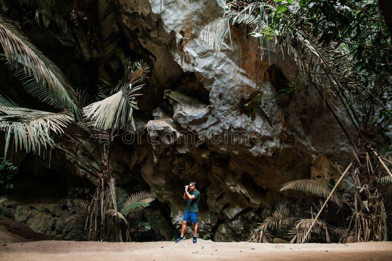 Giovane fotografo maschio asiatico con il panno casuale in caverna t della foresta fotografia stock