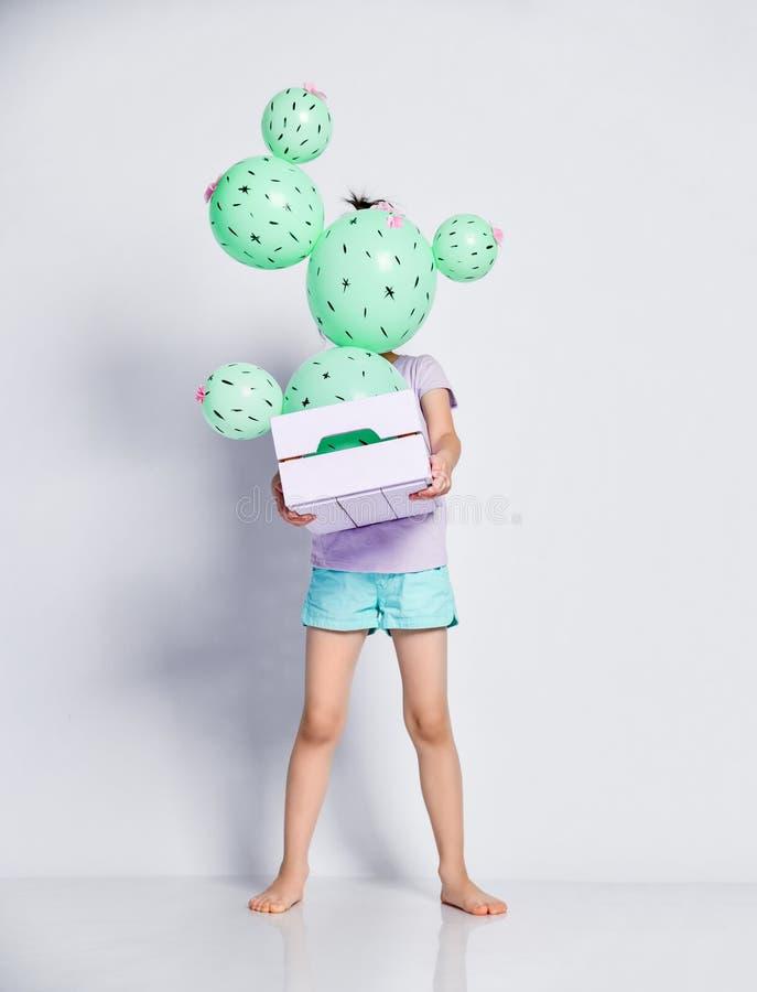 Giovane fronte asiatico del pellame della ragazza dietro il pallone del cactus in contenitore rosa e porpora pastello di fiore fa immagine stock libera da diritti