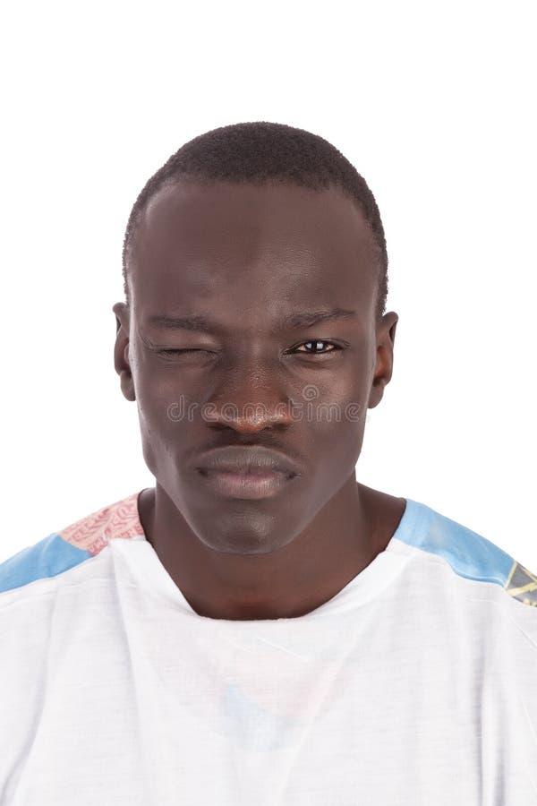 Giovane fronte sudanese bello dell'uomo alla macchina fotografica che sbatte le palpebre occhio giusto fotografia stock