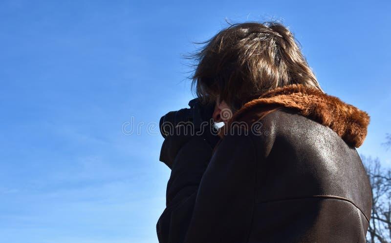 Giovane fucilazione del fotografo di via con la macchina fotografica di DSLR, cielo blu, lampadina, giorno soleggiato fotografia stock