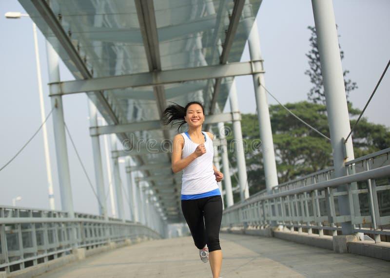 Giovane funzionamento asiatico della donna al footbridg moderno della città fotografie stock libere da diritti