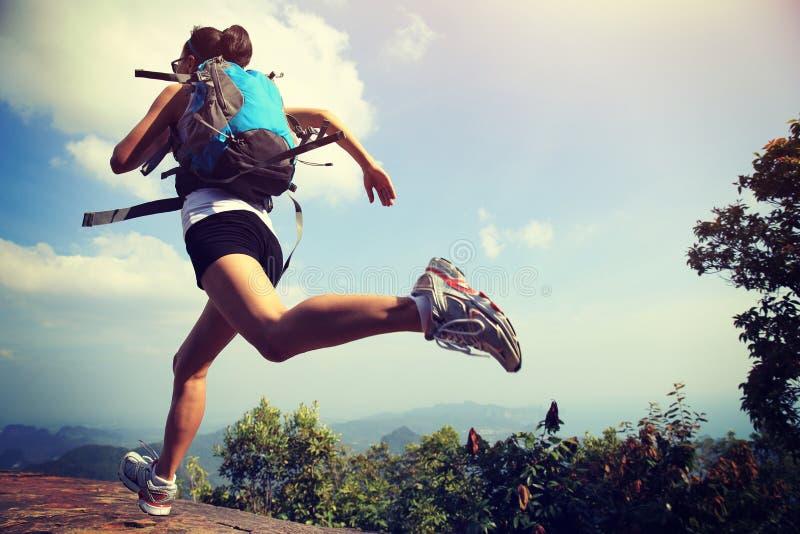 Giovane funzionamento asiatico della viandante della donna sul picco di montagna immagini stock libere da diritti