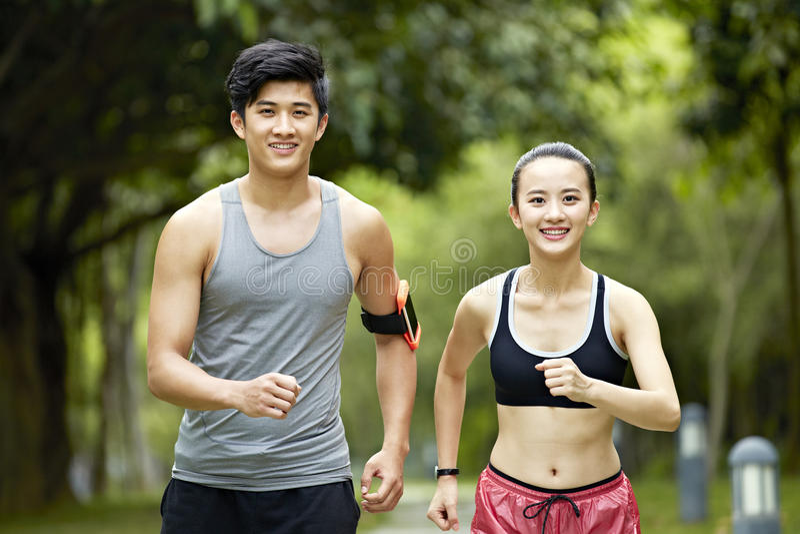 Giovane funzionamento asiatico delle coppie che pareggia in un parco fotografie stock libere da diritti