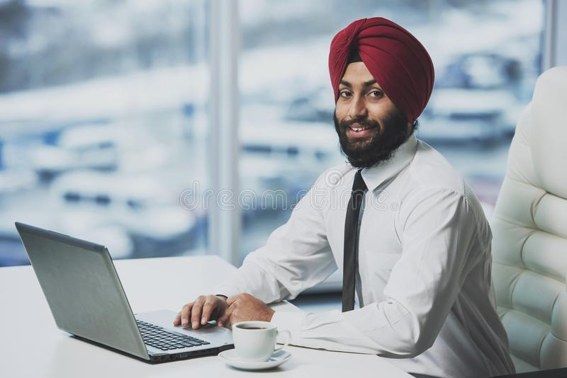 Giovane funzionamento barbuto indiano dell'uomo d'affari fotografia stock