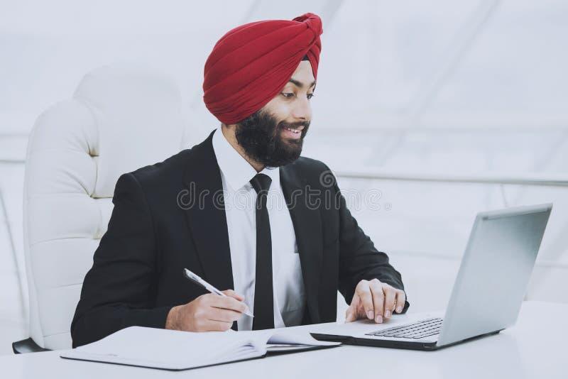 Giovane funzionamento barbuto indiano dell'uomo d'affari fotografie stock