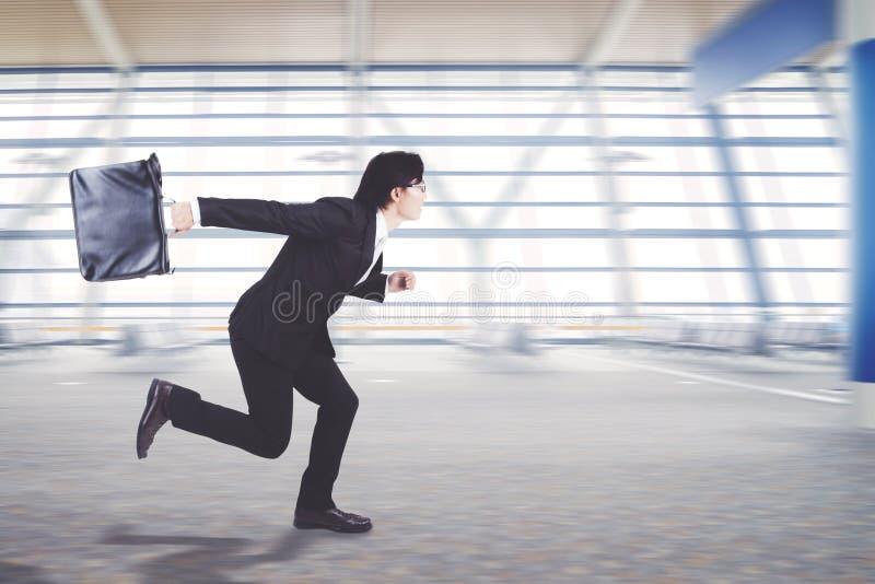 Giovane funzionamento dell'uomo d'affari sul terminale di aeroporto immagine stock libera da diritti