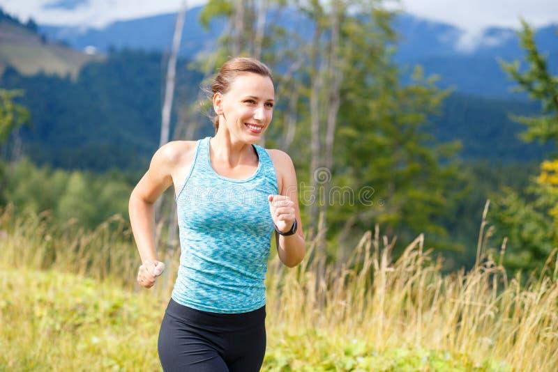 Giovane funzionamento esile della donna in montagne di estate immagine stock