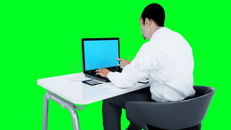 Giovane funzionamento occupato dell'uomo d'affari Maschio africano che esamina lo schermo del computer portatile sullo scrittorio royalty illustrazione gratis
