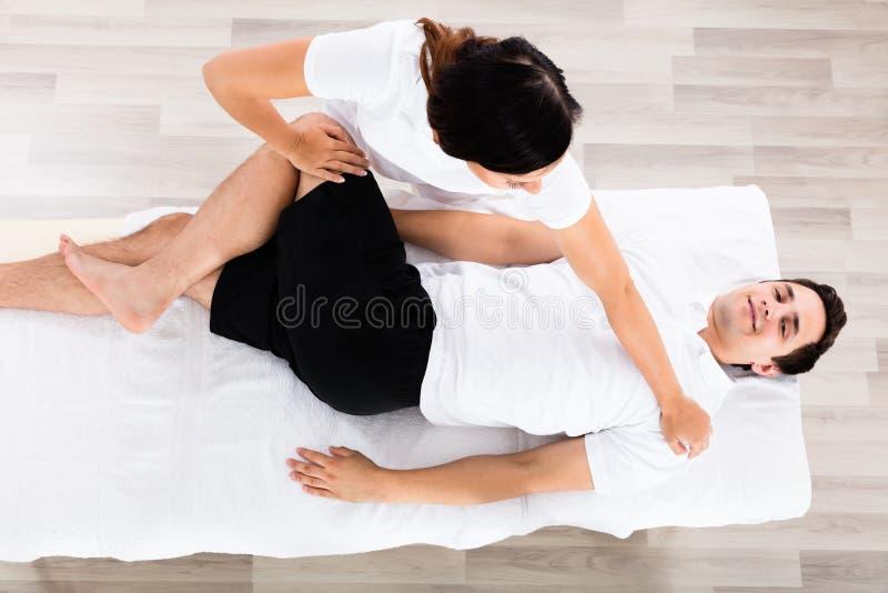 Giovane gamba femminile del ` s di Massaging Relaxed Man del terapista immagine stock