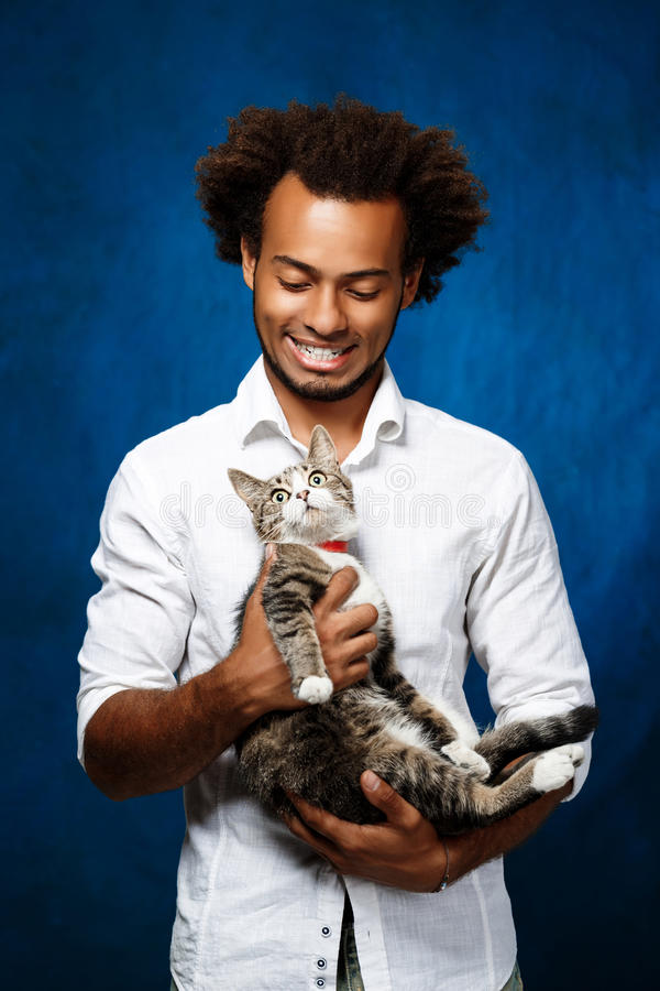 Giovane gatto africano bello della tenuta dell'uomo sopra fondo blu fotografia stock libera da diritti