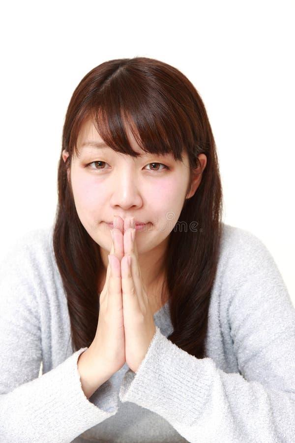 Giovane giapponese che woman folding le sue mani nella preghiera fotografie stock libere da diritti