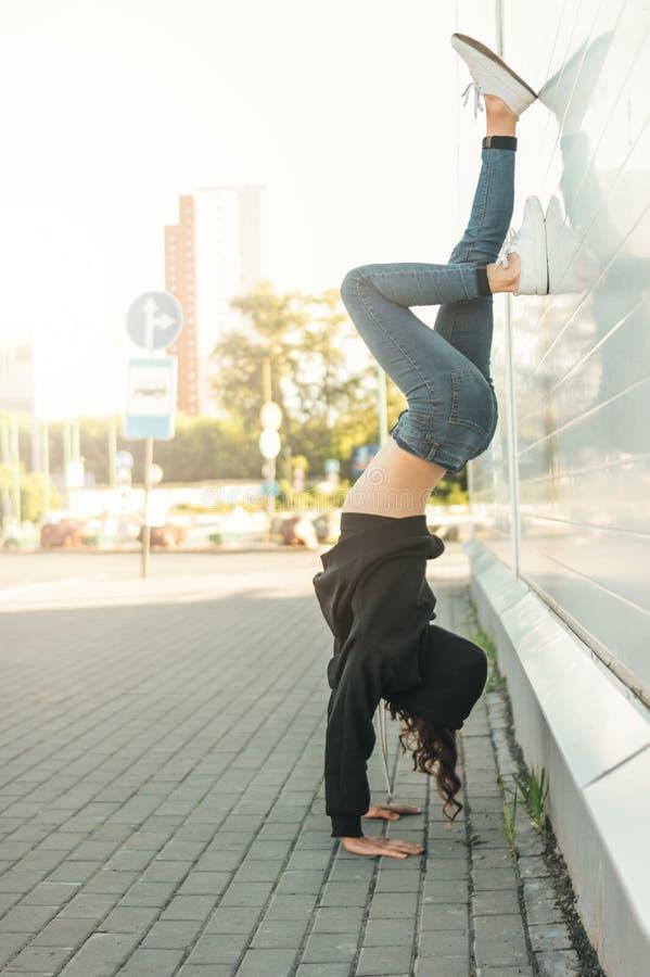 Giovane ginnasta castana del ballerino della via della donna che sta sulle sue armi sulla città immagine stock libera da diritti