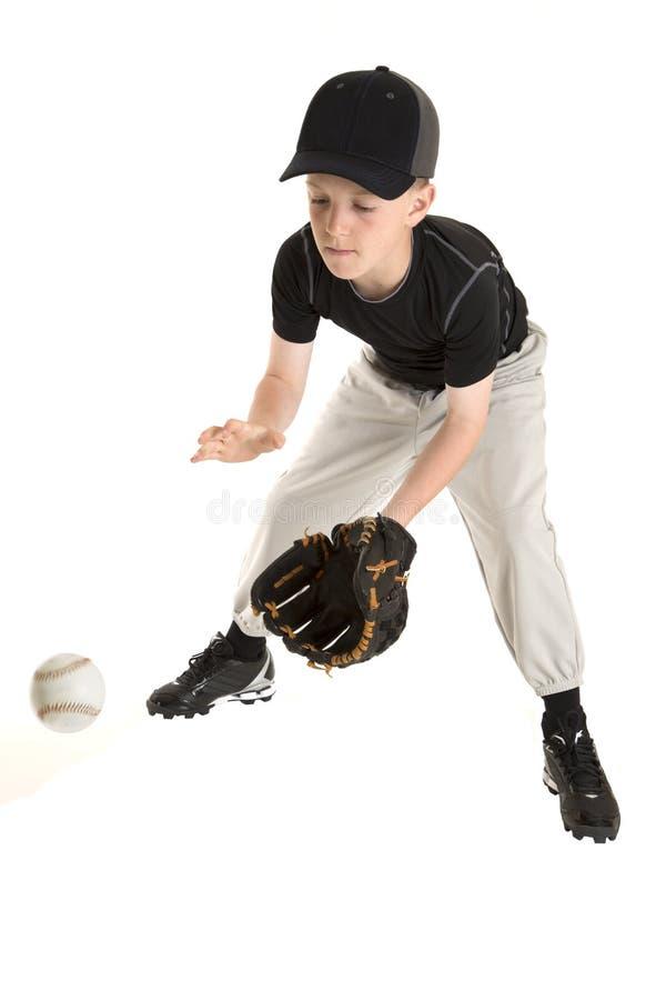 Giovane giocatore di baseball caucasico che prende un grounder fotografia stock