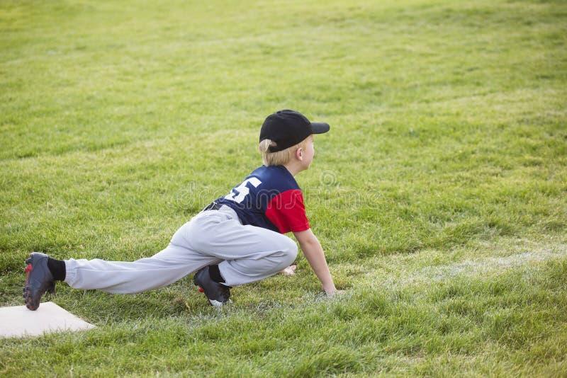 Giovane giocatore di baseball del ragazzo che aspetta sulla terza base immagine stock