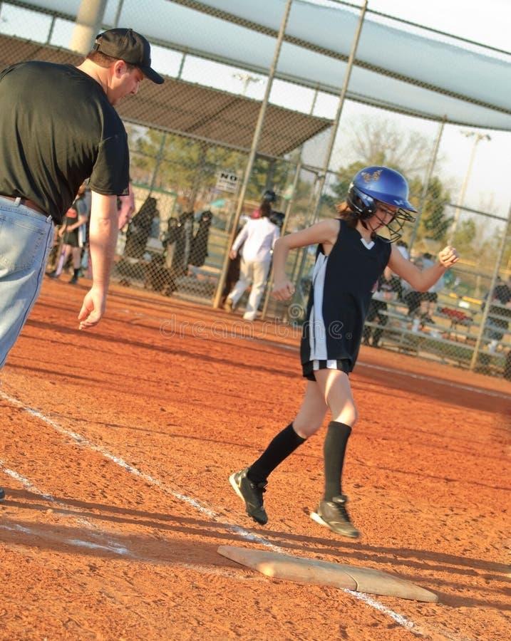 Giovane giocatore di softball che funziona per basare fotografia stock libera da diritti