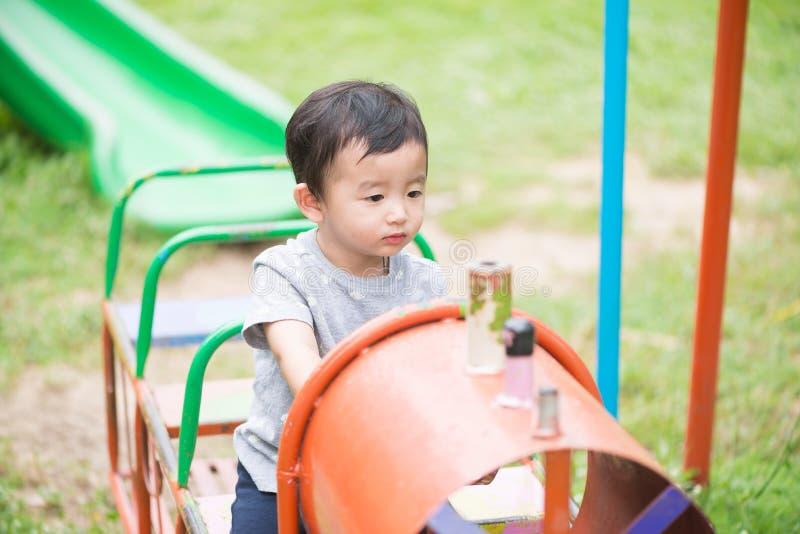 Giovane gioco asiatico del ragazzo un treno del ferro che oscilla al und del campo da giuoco immagini stock