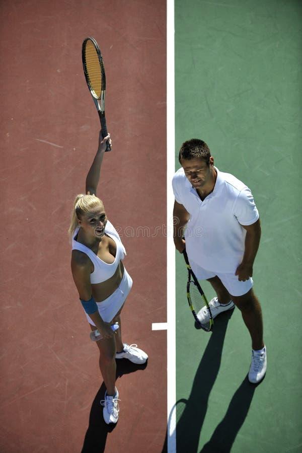 Giovane gioco felice di tennis del gioco delle coppie esterno immagini stock libere da diritti
