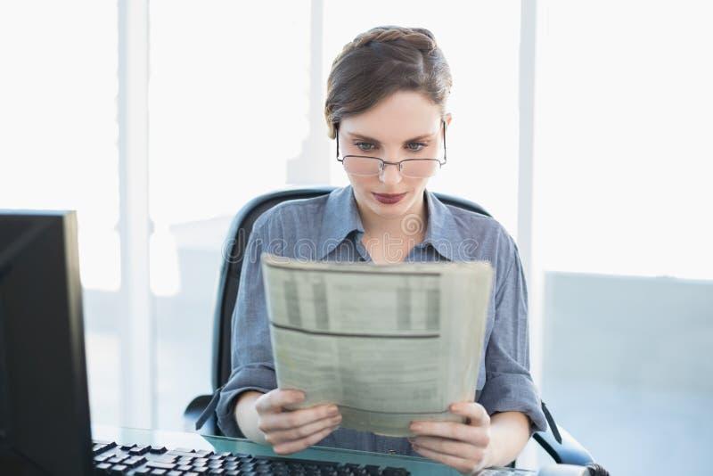 Giovane giornale concentrato della lettura della donna di affari che si siede al suo scrittorio immagini stock