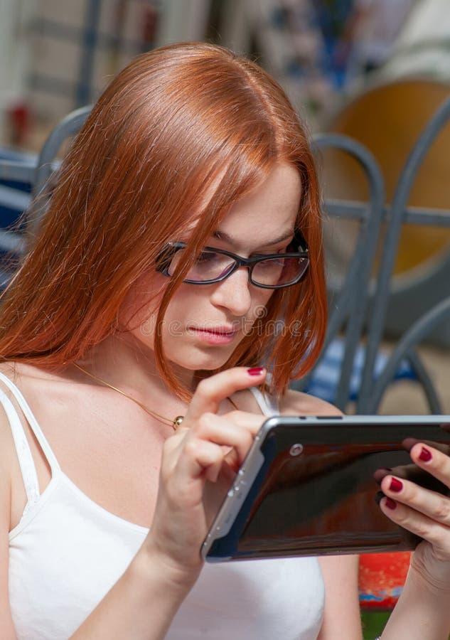 Giovane giovane donna della testarossa con un compressa-pc nel parco che pende come fa scorrere facendo uso dello schermo attivab fotografie stock