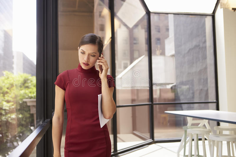 Giovane giovane donna di affari bianca che utilizza telefono nell'ufficio moderno fotografie stock