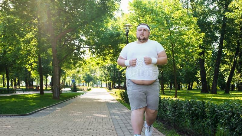 Giovane grasso che pareggia nel parco, concetto di obesità, lottante con l'insicurezza fotografie stock