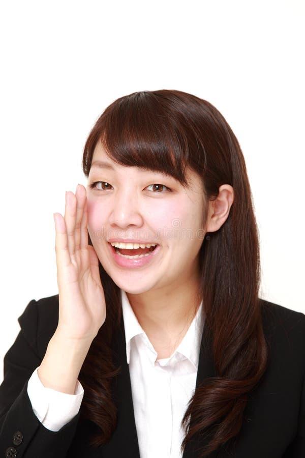 Giovane grido giapponese della donna di affari qualcosa fotografia stock