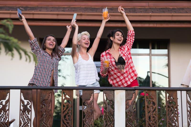 Giovane gruppo allegro sulle mani sollevate balcone, bella comunicazione sorridente felice delle ragazze degli amici della donna fotografie stock