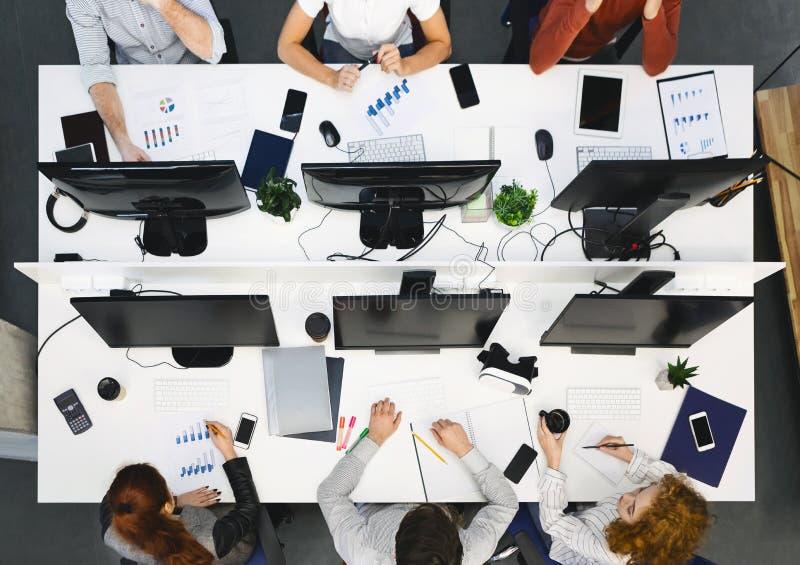 Giovane gruppo che lavora ai computer all'ufficio moderno immagini stock libere da diritti